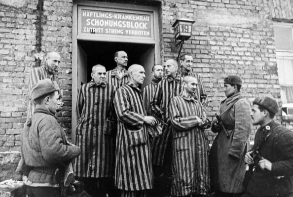 Soviet red army soldiers of the first Ukrainian Front with liberated prisoners of the Auschwitz Concentration Camp in 1945. (Photo by: Sovfoto/Universal Images Group via Getty Images)
