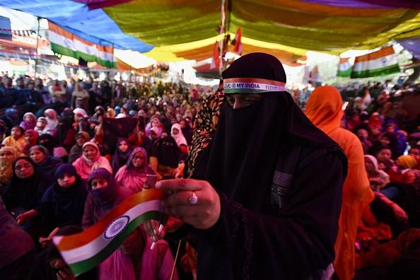 A woman protester carries Indian flag as she clebrates the 71st Republic Day during the ongoing protests against CAA, NRC and NPR at Shaheen Bagh.