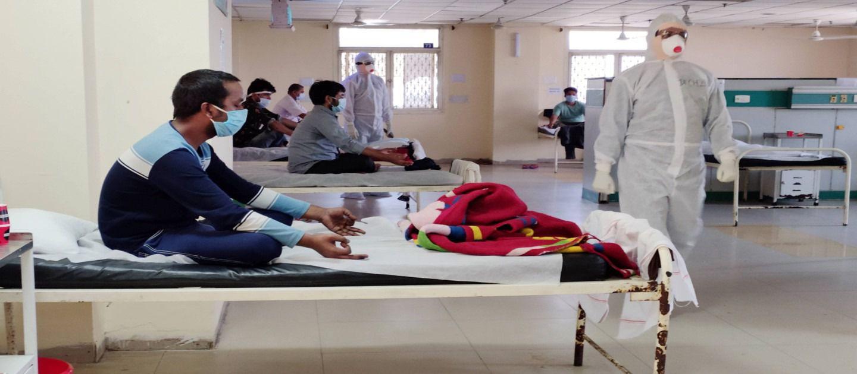 दिल्ली के एक अस्पताल में भर्ती कोरोना संक्रमित लोगों को योग करवाते अस्पताल के कर्मचारी.