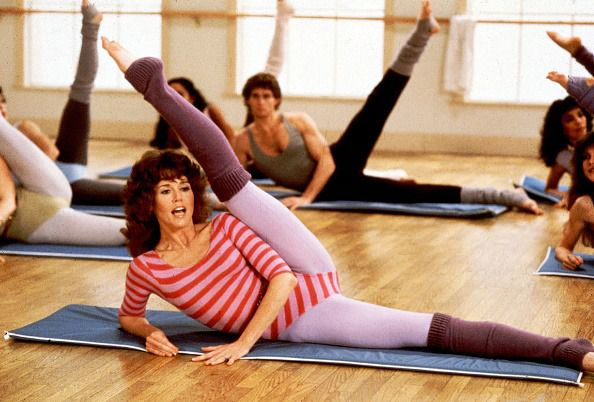Along with unidentified others, American actress Jane Fonda (fore) exercises during a photo shoot for 'Jane Fonda's Workout Book,' Los Angeles, California, 1981. (Photo by Steve Schapiro/Corbis via Getty Images)